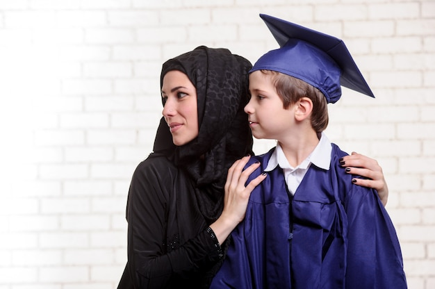 Arabische moeder poseren met afgestudeerde zoon