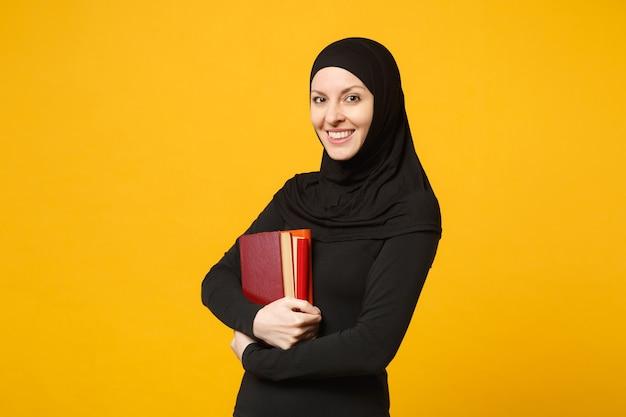 Arabische moslim student meisje in hijab zwarte kleding houdt boeken geïsoleerd op gele muur portret. mensen religieuze levensstijl, onderwijs op de middelbare school concept. .