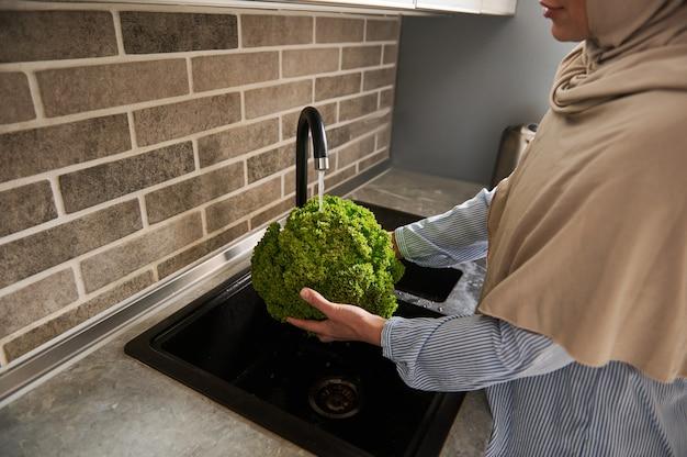 Arabische moslimvrouw in hijab slablaadjes wassen in de keuken. detailopname.