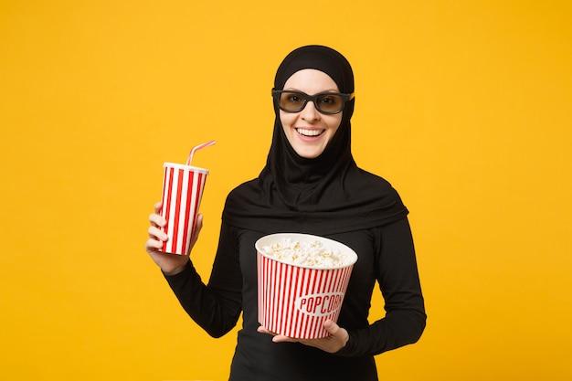Arabische moslimvrouw in hijab zwarte kleding 3d imax bril kijken film film houd popcorn, kopje frisdrank geïsoleerd op gele muur portret. mensen levensstijl concept. .