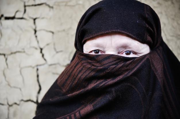 Arabische moslimvrouw op gebarsten muur