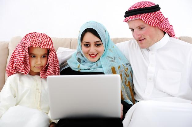 Arabische ouders en kleine jongen thuis met laptopcomputer