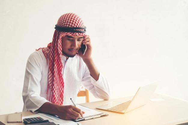 Arabische saoedi-arabische man die online werkt met een laptop en belt