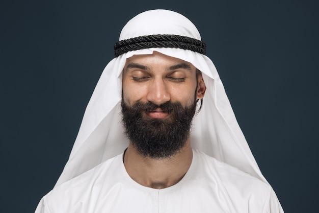 Arabische saoedische man op donkerblauwe studioachtergrond