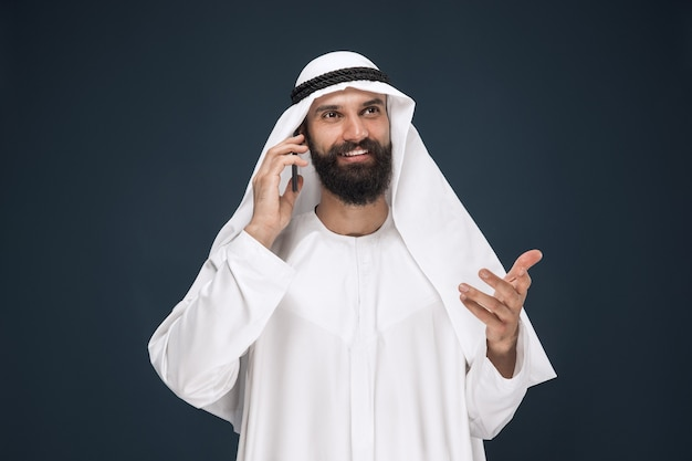 Arabische saudi man op donkerblauwe studio achtergrond