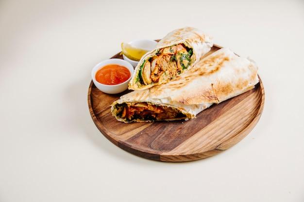 Arabische shaurma met saus op een houten bord.