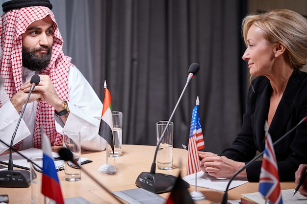 Arabische sjeik-executive luistert aandachtig naar een van de sprekers die de afgevaardigden rapporteren, luisterend naar ideeën voor succesinvesteringen in een lichte, moderne kantoorruimte. mensen in formele kleding op persconferentie.