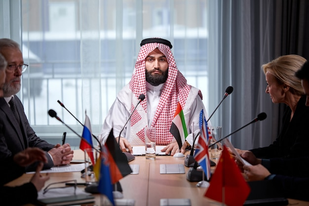 Arabische sjeik man presenteert zijn ideeën aan diverse multi-etnische collega's en luistert naar ideeën voor succesinvesteringen in lichte, moderne kantoorruimte, gebruik microfoon. ontmoeting zonder banden