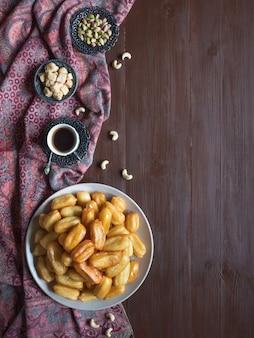 Arabische snoepviering eid ramadan. traditioneel turks dessert tulumba - tulumba tatlisi op houten achtergrond