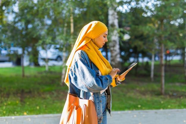 Arabische studente. mooie moslim vrouwelijke student helder gele hijab houden tablet dragen.