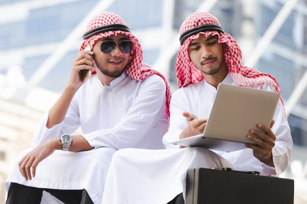 Arabische telefoon van de bedrijfsmensenvraag die aan taplet in de stad werken