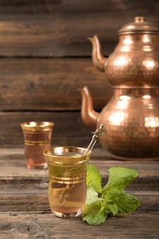 Arabische thee in glazen met theepotten op tafel