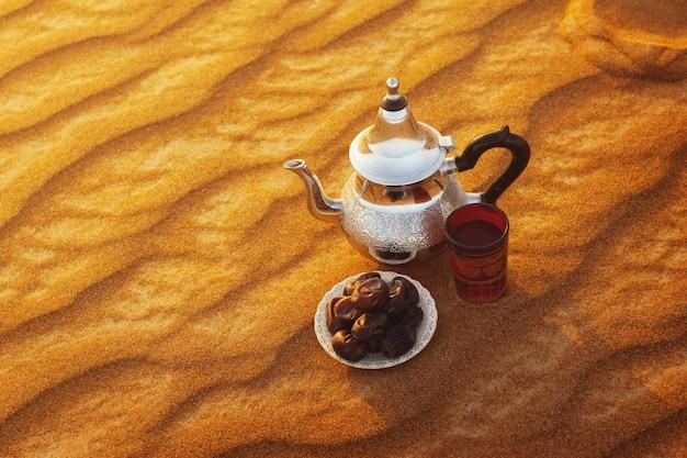 Arabische theepot, beker en dadels staan op het zand in de woestijn