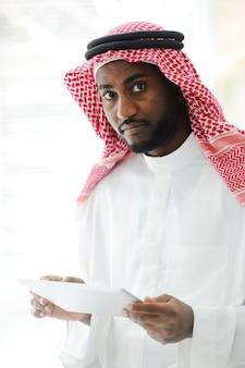 Arabische uitvoerende persoon die tablet gebruiken op kantoor