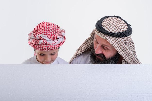 Arabische vader met zoon die een witte poster vasthoudt en zijn tong uitsteekt stock foto