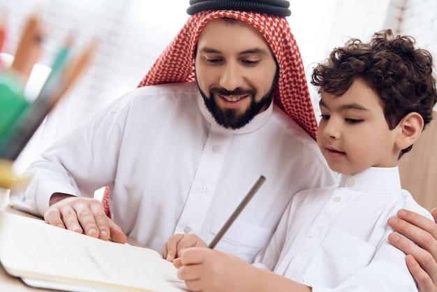 Arabische vader onderwijst kleine zoon van spellingsbrieven.