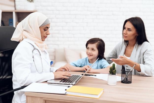 Arabische vrouw arts die een diagnose van een zieke jongen typt.