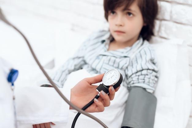 Arabische vrouw arts meet de druk van een zieke jongen.