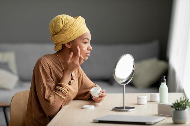 Arabische vrouw die room in haar gezicht aanbrengt. schoonheidsbehandeling