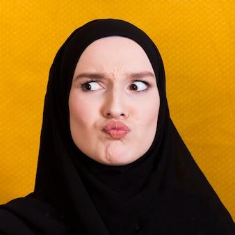 Arabische vrouw die verwarde gelaatsuitdrukking op zwarte achtergrond maakt