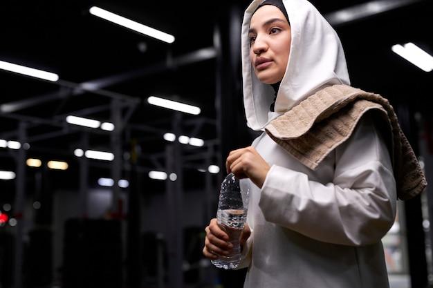 Arabische vrouw in hijab neemt een slokje water tijdens training in de sportschool, neemt een pauze, rust uit, draagt witte sportieve hijab