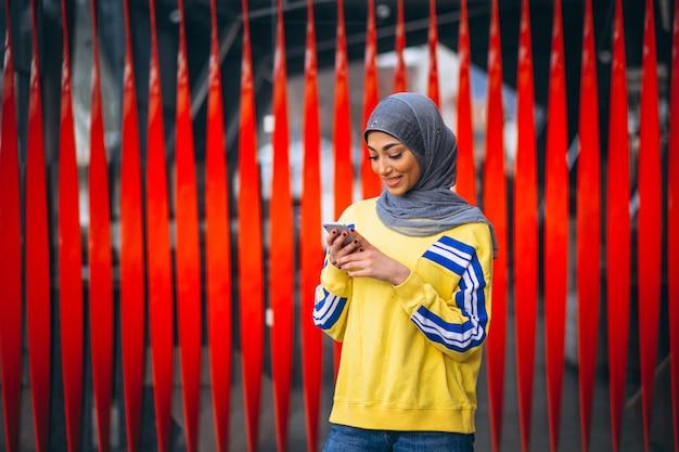 Arabische vrouw in hijab ouside in de straat die telefoon met behulp van