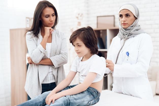 Arabische vrouwelijke arts onderzoekt een zieke jongen