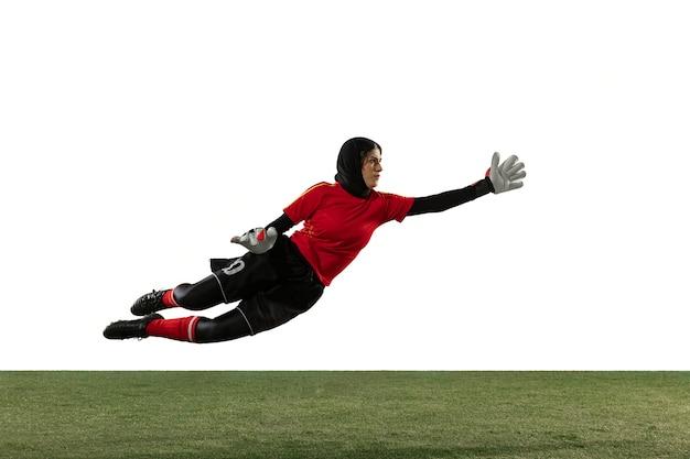 Arabische vrouwelijke voetbal of voetballer, doelman op witte studioachtergrond. jonge vrouw bal vangen, opleiding, doelen in beweging en actie te beschermen. concept van sport, hobby, gezonde levensstijl. Gratis Foto