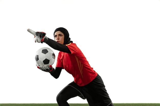 Arabische vrouwelijke voetbal of voetballer, doelman op witte studioachtergrond. jonge vrouw die pas geeft, emotioneel gebaren, die doelstellingen voor team beschermt. concept van sport, hobby, gezonde levensstijl.