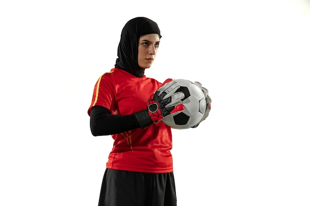 Arabische vrouwelijke voetbal of voetballer, doelman op witte studioachtergrond. jonge vrouw poseren zelfverzekerd met bal, doelen voor team te beschermen.
