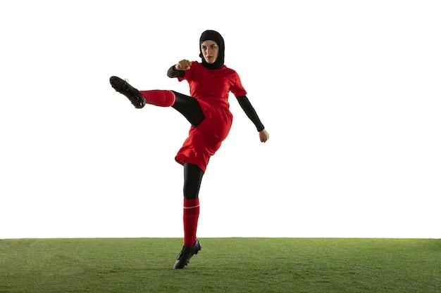 Arabische vrouwelijke voetballer die op witte studiomuur wordt geïsoleerd