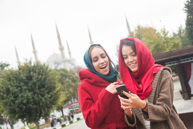 Arabische vrouwen dragen sluier met behulp van een slimme telefoon in istanbul