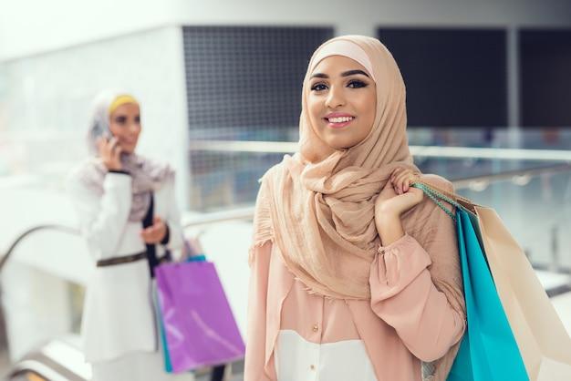 Arabische vrouwen met glimlach op gezicht in winkelcentrum.