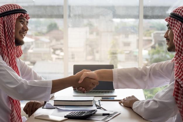 Arabische zakenlieden die overhandigen een overeenkomstonderhandeling aan succes