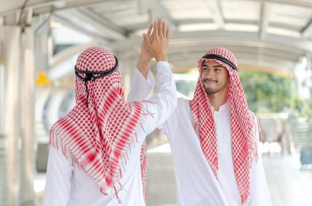 Arabische zakenman die handen raakt samen bij het gebied van de gangmanier.