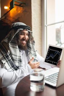 Arabische zakenman die in het zakencentrum van het kantoor werkt met behulp van de levensstijl van apparatenm gadgets