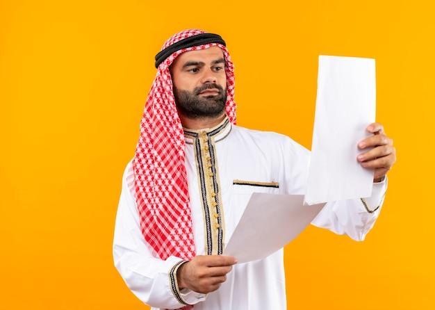 Arabische zakenman die in traditionele slijtage documenten in handen bekijkt met ernstig gezicht dat zich over oranje muur bevindt