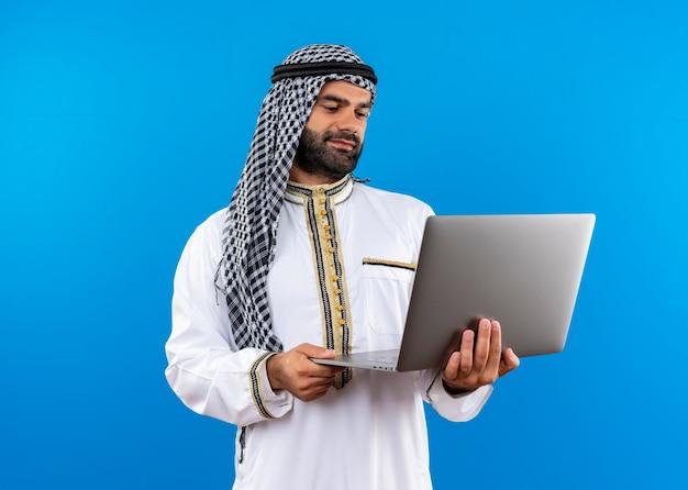 Arabische zakenman die in traditionele slijtage laptop houdt die het met glimlach op gezicht bekijkt die zich over blauwe muur bevindt