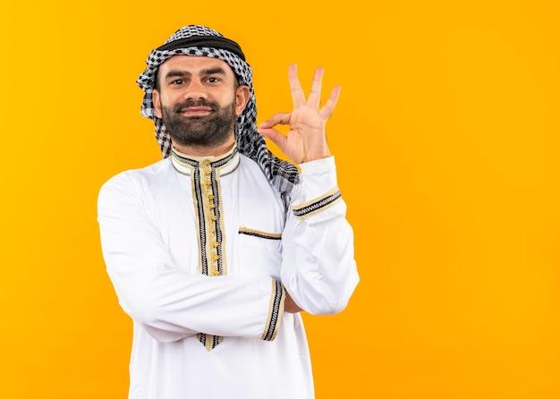 Arabische zakenman die in traditionele slijtage zeker glimlachen doet ok teken dat zich over oranje muur bevindt