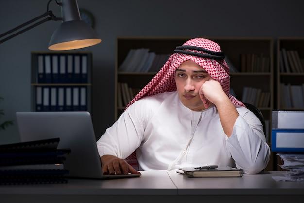 Arabische zakenman die laat in bureau werkt