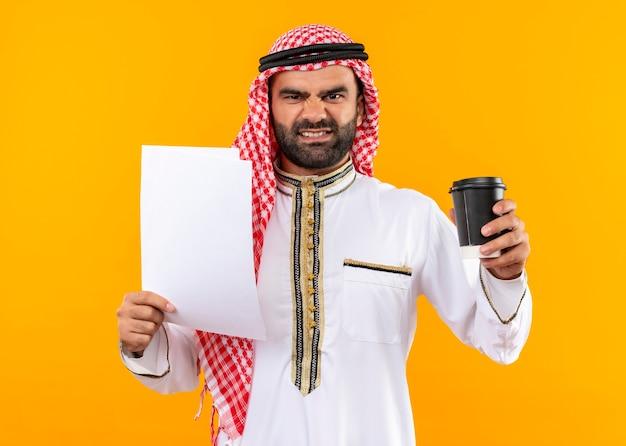 Arabische zakenman in traditionele dragende documenten en koffiekop met boos gezicht dat zich over oranje muur bevindt