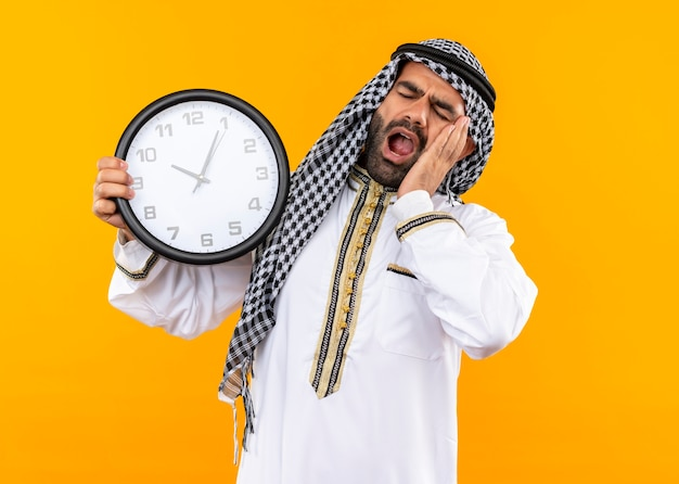 Arabische zakenman in traditionele kleding die muurklok houdt die zijn hoofd op zijn handpalm leunt en er moe uitziet, wil slapen geeuwend over oranje muur staan