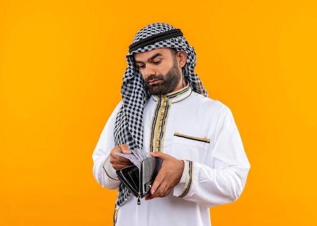 Arabische zakenman in traditionele slijtage die contant geld in zijn portefeuille bekijkt met ernstig gezicht dat zich over oranje muur bevindt