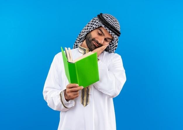 Arabische zakenman in traditionele slijtage die een open boek houdt en ernaar kijkt met een glimlach op gezicht over blauwe muur