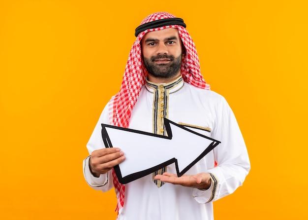 Arabische zakenman in traditionele slijtage die grote pijl naar rechts met glimlach op gezicht houdt die zich over oranje muur bevindt