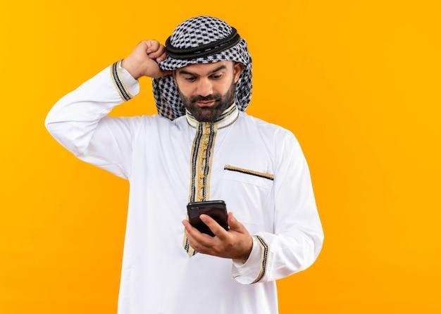 Arabische zakenman in traditionele slijtage die het scherm van zijn smartphone bekijkt die verward zich over oranje muur bevindt