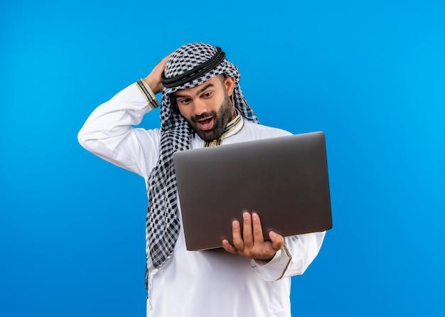 Arabische zakenman in traditionele slijtage die laptop bekijkt die het verrast en gelukkig bekijkt status over blauwe muur
