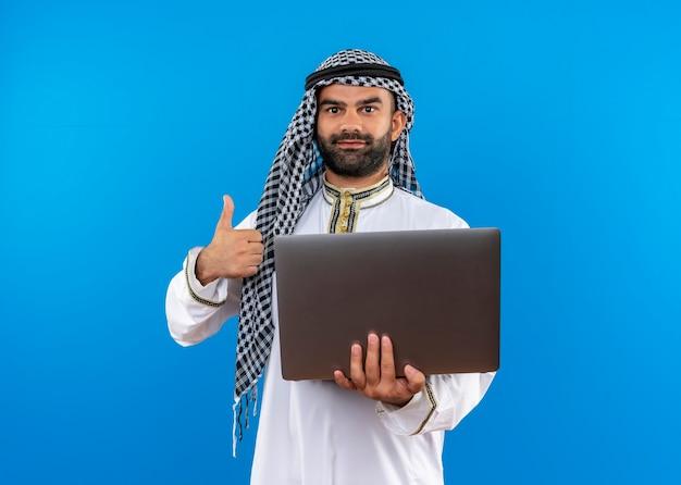 Arabische zakenman in traditionele slijtage die laptop glimlachend toont duimen die omhoog zich over blauwe muur bevinden