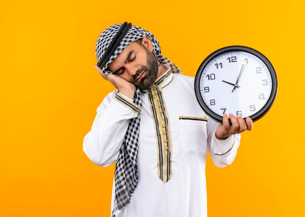 Arabische zakenman in traditionele slijtage die muurklok houdt die zijn hoofd op zijn handpalm leunt die er moe uitziet, wil staande over oranje muur slapen
