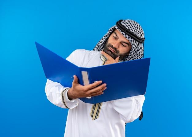 Arabische zakenman in traditionele slijtage die open map houdt die ernaar kijkt met een ernstig gezicht dat zich over blauwe muur bevindt